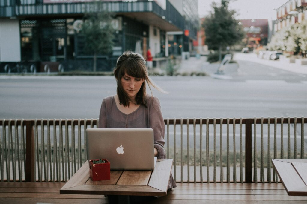 woman in gray shirt sitting on bench in front of MacBook